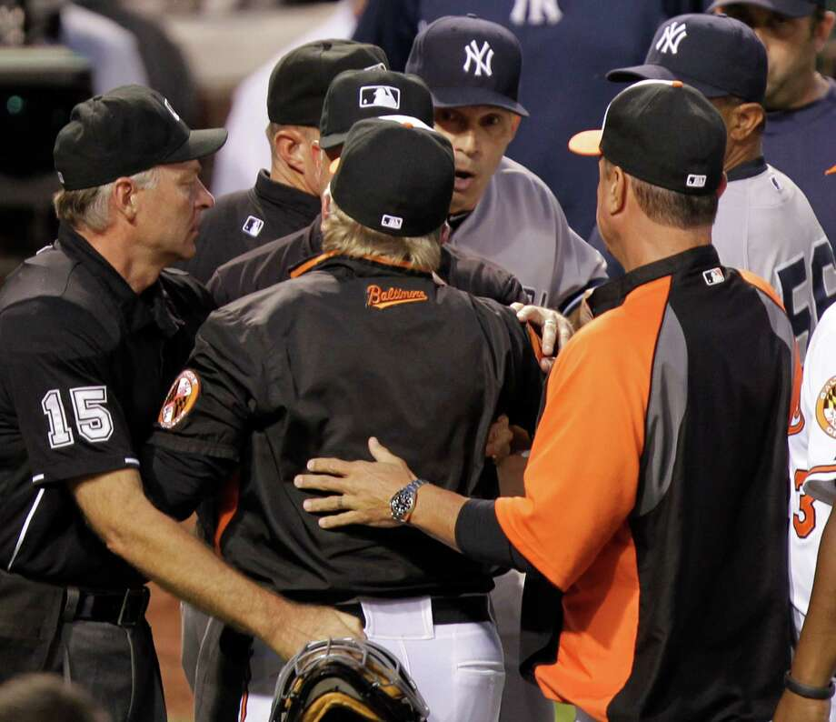 Baltimore Orioles manager Buck Showalter, center, argues with New York Yankees manager Joe Girardi, center left, at the end of the first inning of a baseball game, Monday, Sept. 9 2013, in Baltimore. (AP Photo/Luis M. Alvarez) ORG XMIT: MDLA105 Photo: Luis M. Alvarez / FR596 AP