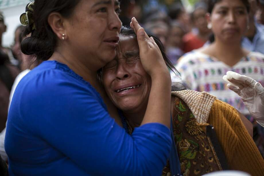 An unidentified woman is comforted as she weeps for a dead relative who was a passenger on a bus that plunged into a deep river canyon in San Martin Jilotepeque, northwest Guatemala, Monday, Sept. 9, 2013. Dozens were killed and at least 45 injured people had been taken to hospitals. (AP Photo / Luis Soto) Photo: Luis Soto, Associated Press