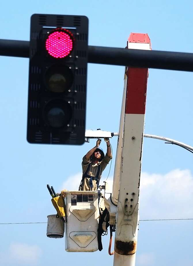 Josh Johnson with UTEC Contruction replaces an HID or High-intensity discharge lamp with a new led light on a lightpole on 13th Street, Monday, Sept. 9, 2013, in Augusta, Ga. (AP Photo/ The Augusta Chronicle, Todd Bennett) Photo: Todd Bennett, Associated Press