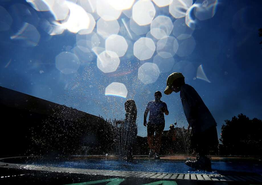 Children take refuge from the heat by playing in the fountain at the Kansas State Fair on Monday, Sept. 9, 2013, in Hutchinson, Kan. (AP Photo/The Hutchinson News, Lindsey Bauman) Photo: Lindsey Bauman, Associated Press