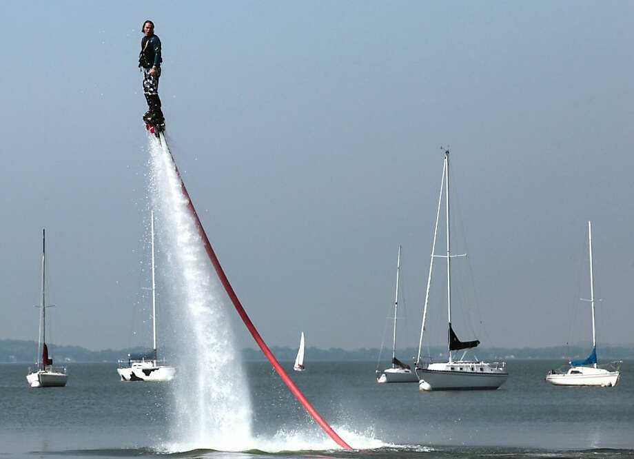 "Will Schmidt flies above Lake Mendota near the UW-Madison campus in Madison, Wis. on a water jet-powered flyboard Monday, Sept. 9, 2013. Schmidt invested in the apparatus after taking an initial test flight a year ago. ""The first day I did it, I quit my job"" said the former entertainment coordinator who is now one of approximately 30 trainers working in the United States. Tethered to a 37-foot fire hose connected to a jet ski, riders are lifted into the air by 1,000 gallons of water per minute which is diverted from the watercraft's engine. ""I can teach anyone to do it in about five minutes"" said Schmidt, whose oldest customer so far has been an 81-year-old man. ""It's kind of unlike anything else. You feel like Iron Man."" (AP Photo/Wisconsin State Journal, John Hart) Photo: John Hart, Associated Press"