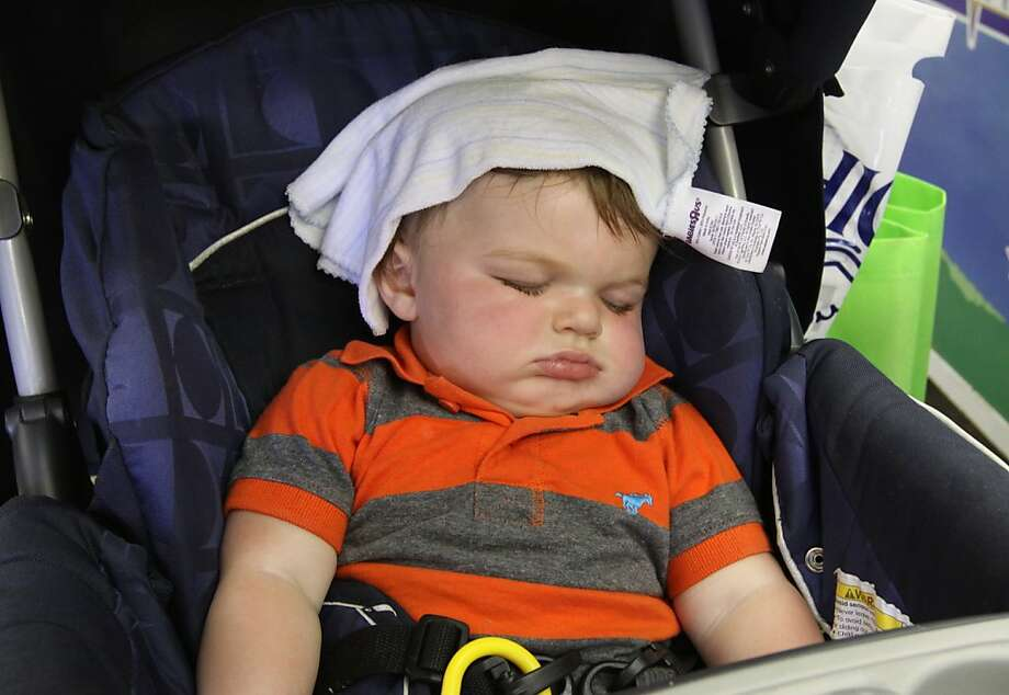 Charlie Roberts, 9 months, keeps cool with a wet towel while taking a nap in the Eisenhower building at the Kansas State Fair on Monday afternoon, Sept. 9, 2013, in Hutchinson, Kan. (AP Photo/The Hutchinson News, Sandra J. Milburn) Photo: Sandra J. Milburn, Associated Press