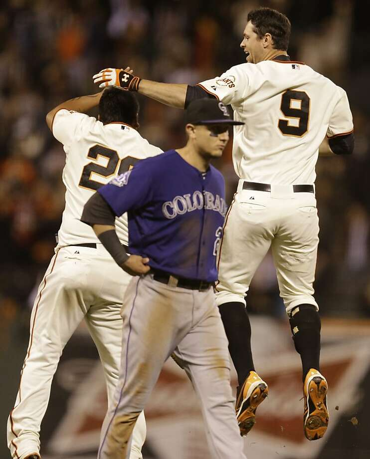 Brandon Belt (9) and Hector Sanchez celebrate behind the Rockies' Troy Tulowitzki after Belt's winning hit. Photo: Ben Margot, Associated Press