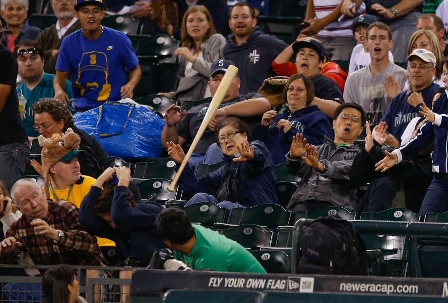 Fans duck out of the way of a flying bat let loose by Kyle Seager of the Mariners in the fifth inning against the Astros. Photo: Otto Greule Jr, Getty Images