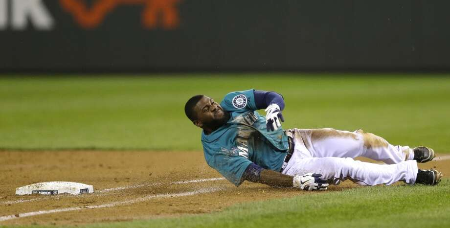 Abraham Almonte of the Mariners reacts after diving for first base in an unsuccessful attempt to avoid a tag by Astros first baseman Brett Wallace (not shown). Photo: Ted S. Warren, Associated Press