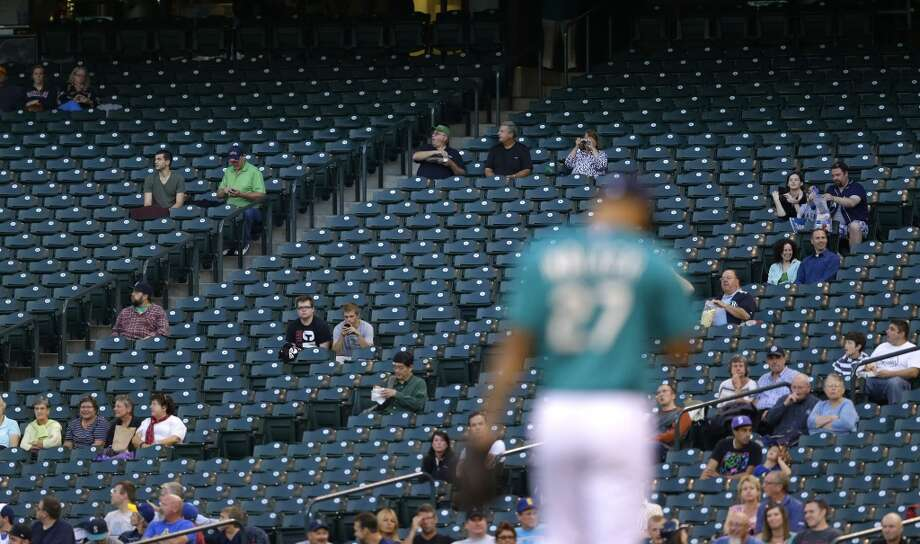 Only a few fans are in the stands near first base at Safeco Field as Mariners starting pitcher Taijuan Walker takes the mound against the Astros. Photo: Ted S. Warren, Associated Press