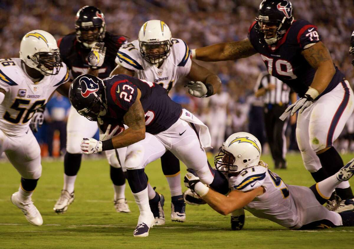 Running back Arian Foster, seeing his first action after sitting out the preseason, is brought down by Chargers linebacker Jonas Mouton.