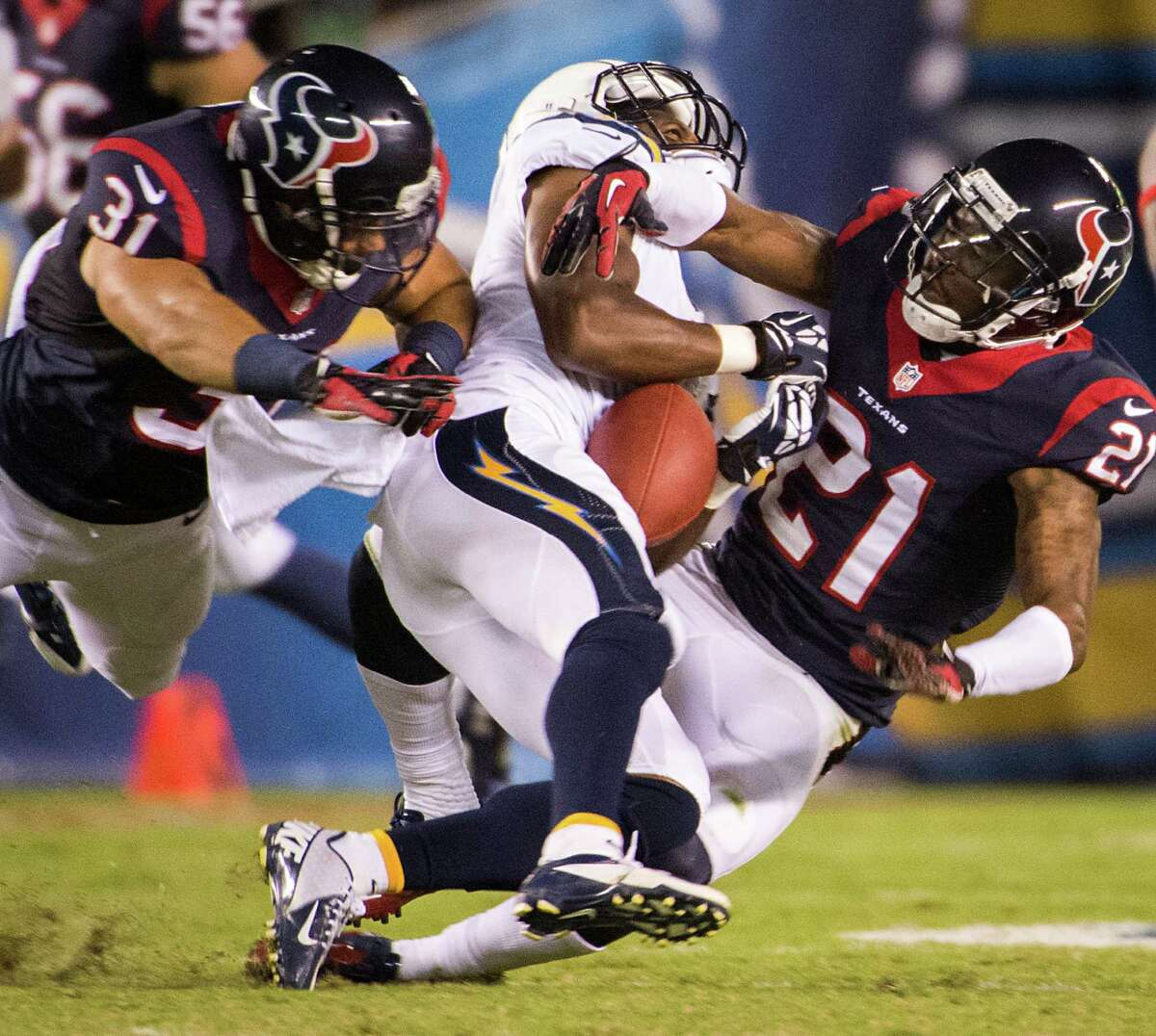 Chargers wide receiver Eddie Royal, center, can't make a catch as he is hit by Texans cornerback Brice McCain (21) and safety Shiloh Keo (31) during the third quarter Monday night.
