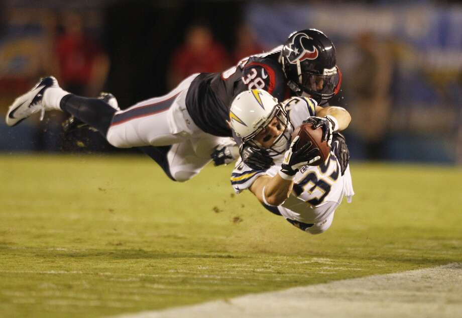 Chargers running back Danny Woodhead dives for extra yardage as he is brought down by Texans free safety Danieal Manning. Photo: Brett Coomer, Houston Chronicle