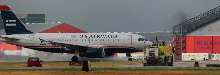 A U.S. Airways passenger jet lands safely at San Antonio International Airport Tuesday, Sept. 10, 2013, as emergency vehicles stand by. Photo: JOHN DAVENPORT, SAN ANTONIO EXPRESS-NEWS / ©San Antonio Express-News/Photo may be sold to the public