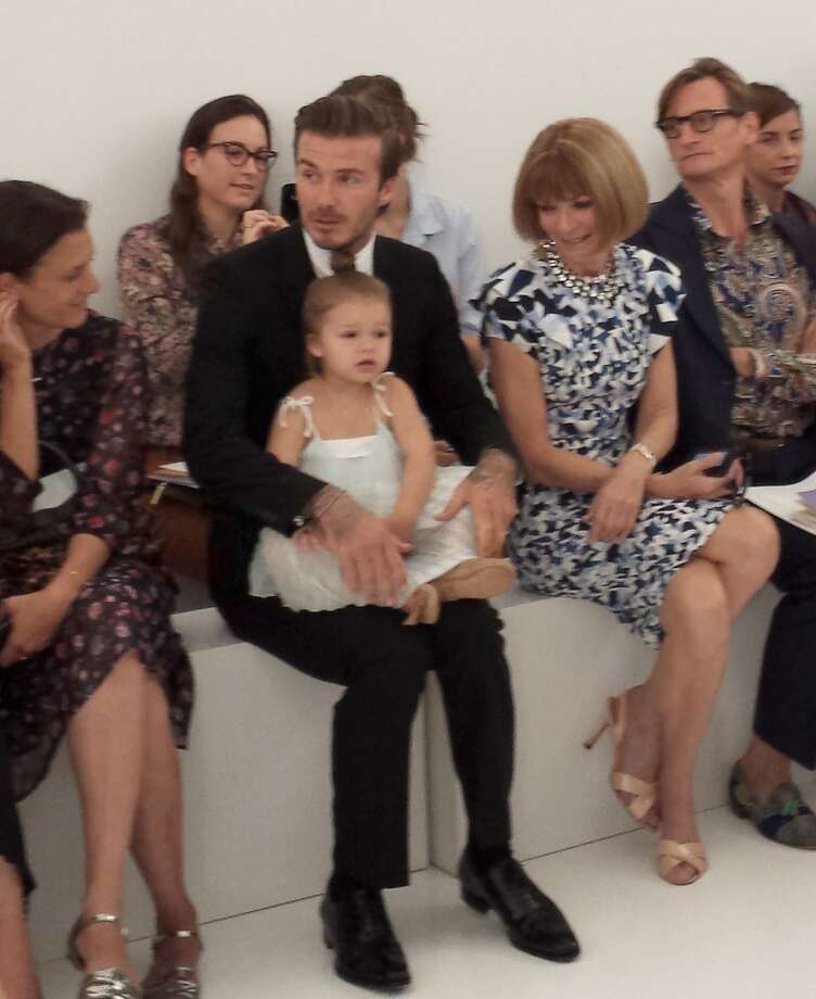 Soccer star David Beckham with daughter Harper and celebrity editor of Vogue Anna Wintour (R) watch as designer wife Victoria Beckham unveils her new collection during the Mercedes-Benz Fashion Week Spring 2014 show on September 8, 2013 in New York. Photo: AFP, AFP/Getty Images