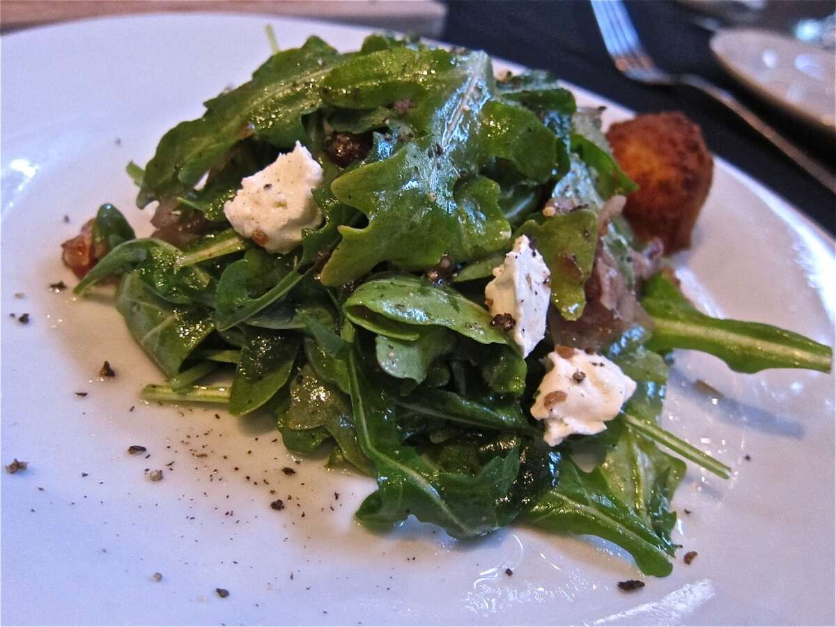 Warm goat cheese salad with Sicilian dates, wild arugula, candied walnuts and pomegranate