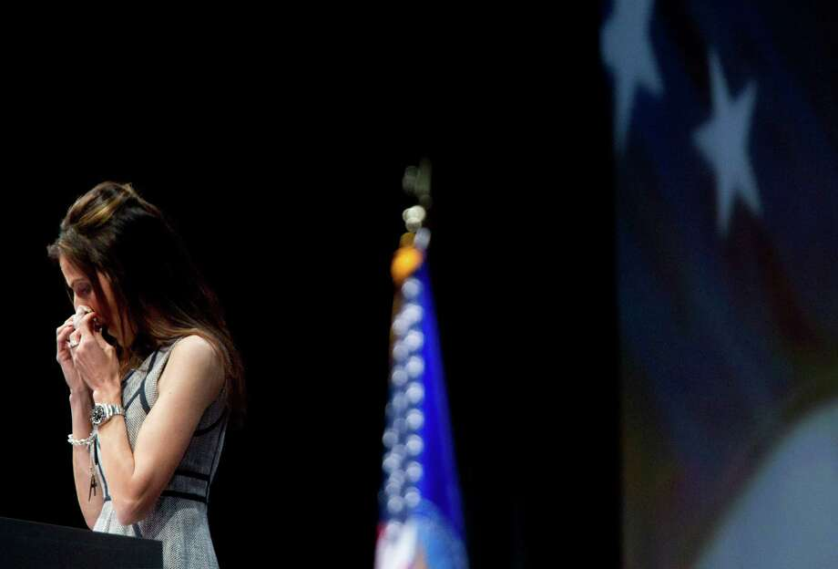 Taya Kyle, the wife of slain Navy SEAL sniper Chris Kyle wipes tears from her eyes as she spoke during the NRA-ILA Leadership Forum at the National Rifle Association's 142 Annual Meetings and Exhibits in the George R. Brown Convention Center Friday, May 3, 2013, in Houston.  The 2013 NRA Annual Meetings and Exhibits runs from Friday, May 3, through Sunday, May 5.  More than 70,000 are expected to attend the event with more than 500 exhibitors represented. The convention will features training and education demos, the Antiques Guns and Gold Showcase, book signings, speakers including Glenn Beck, Ted Nugent and Sarah Palin as well as NRA Youth Day on Sunday ( Johnny Hanson / Houston Chronicle ) Photo: Johnny Hanson, Staff / © 2013  Houston Chronicle