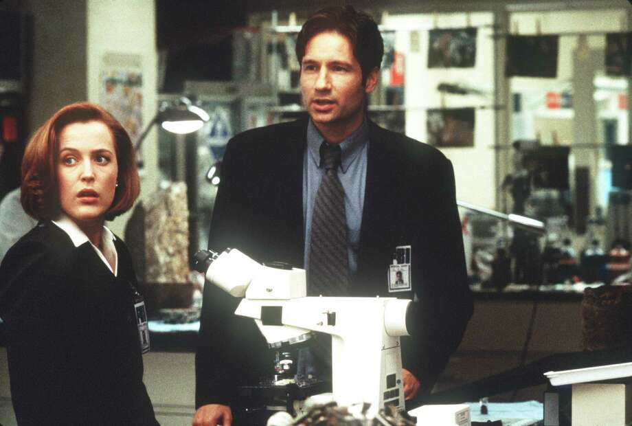 "HOUCHRON CAPTION (06/18/1998): Gillian Anderson and David Duchovny search for the truth in ""The X-Files"" movie. Photo: Merrick Morton, Twentieth Century Fox / handout slide"