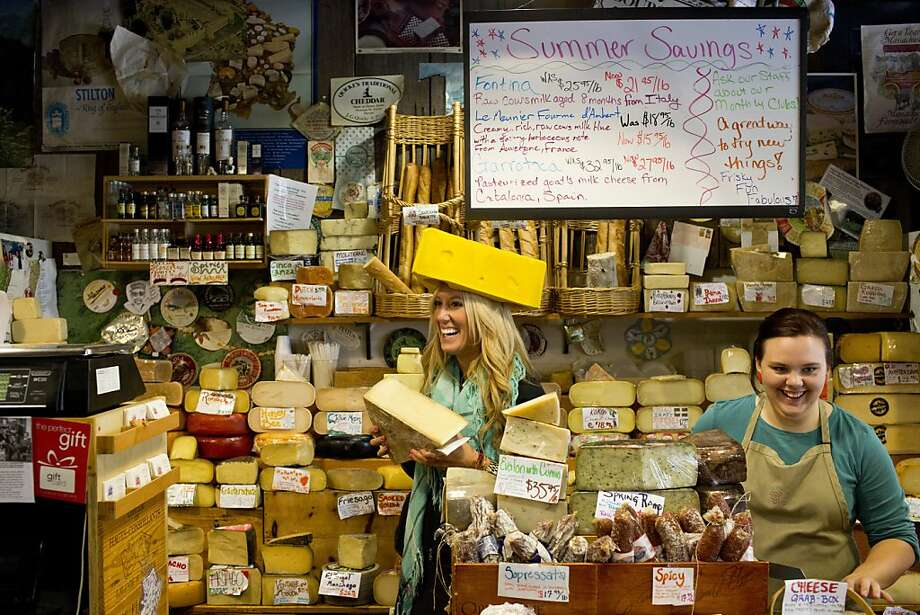 Customers often come behind the counter and pose for photos wearing the cheesehead hat, like Shanda Palmer at the Cheese Shop in Carmel. Photo: Jason Henry, Special To The Chronicle
