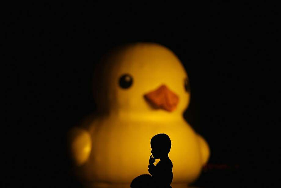 Rubber Ducky, you're the one. Sixty feet tall, weigh a ton: A boy sits on his father's shoulders to get a good