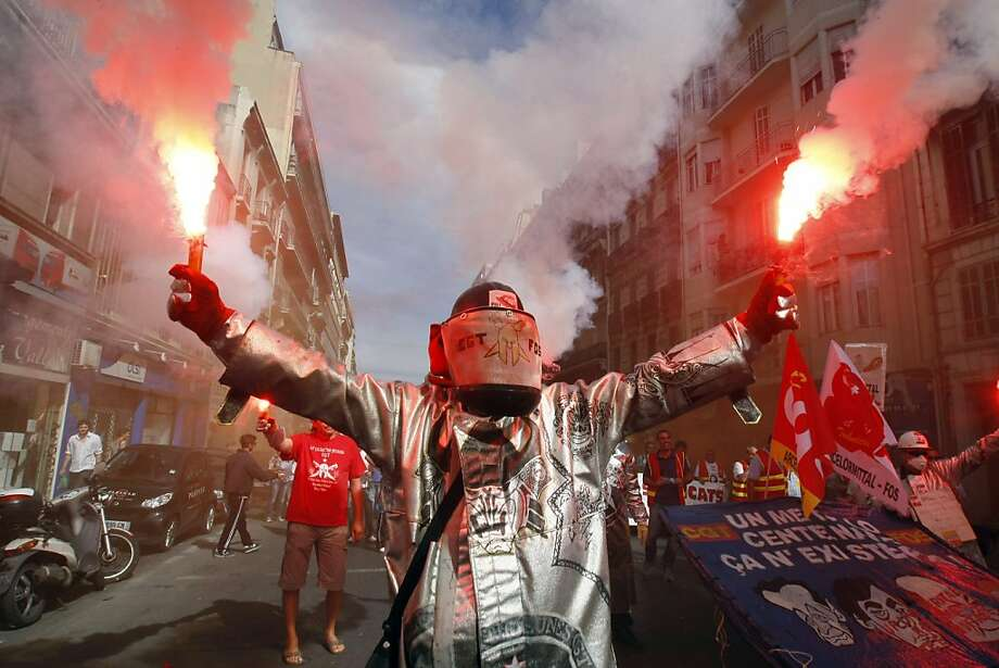 Labor unrest flares up:Steelworkers from the ArcelorMittal steel plant in Fos-sur-Mer, France, carry a torch (or two) against government-mandated pension reform during a nationwide day of protest in Marseille. Photo: Claude Paris, Associated Press
