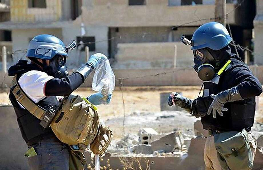 In a citizen journalism image, members of a U.N. investigation team take samples last month in the Damascus countryside near a part of a missile thought to be used in a chemical attack. Photo: Uncredited, Associated Press