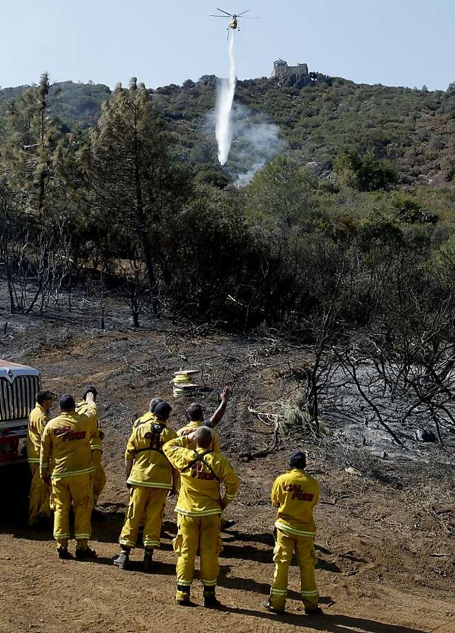 Firefighters watch as a helicopter drops water on small hot spots near the summit of Mount Diablo. The Morgan Fire on the mountain's eastern slope is coming under control. Photo: Michael Macor, The Chronicle