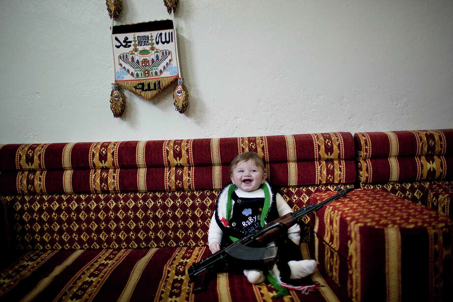 6-months old Maher, laughs as the child is placed to pose with a machine gun placed by supporters of the Free Syrian Army, inside a house near Idlib, Syria, Thursday, Feb. 23., 2012. Photo: Rodrigo Abd, ASSOCIATED PRESS / AP2012
