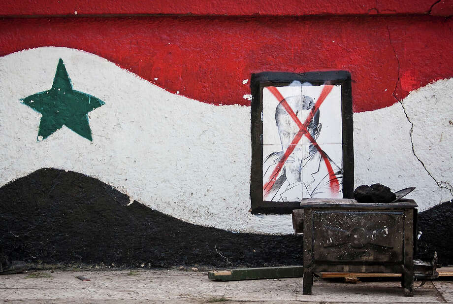 This Sunday, Dec. 16, 2012 photo, shows a damaged portrait of former Syrian President Hafez Assad at the entrance of a military academy besieged by rebels during heavy clashes with government forces north of Aleppo, Syria. Photo: Narciso Contreras, ASSOCIATED PRESS / AP2012