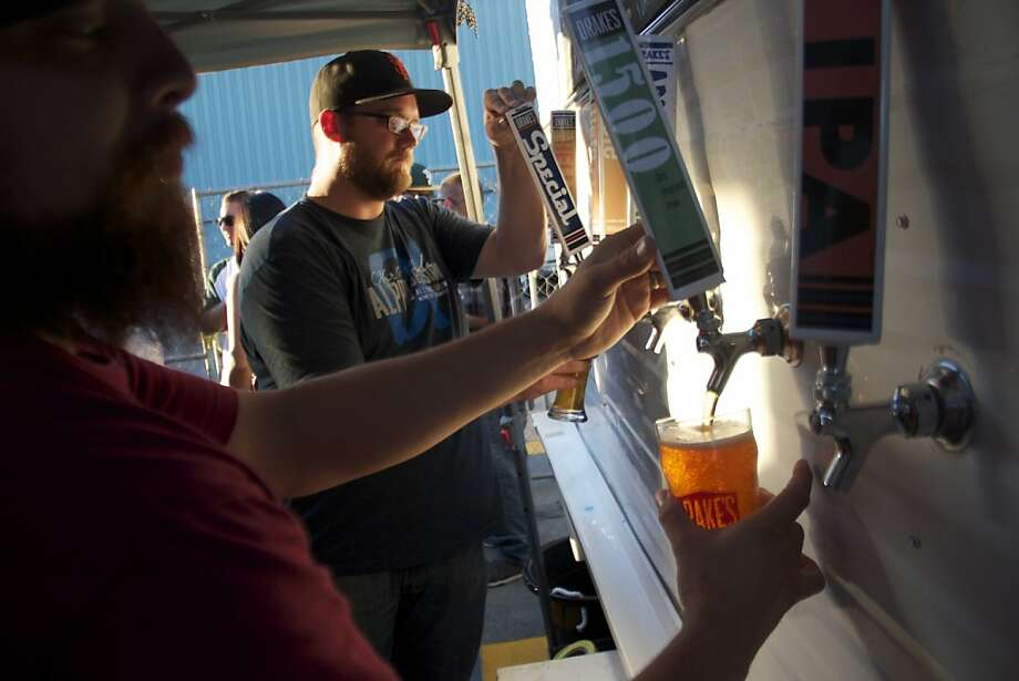 Monte Cano (foreground) and Jeffrey McClure help pour beers from about a dozen on tap at Drake's First Friday in San Leandro. Photo: Kelsey Williams, Drake's Brewing Co.
