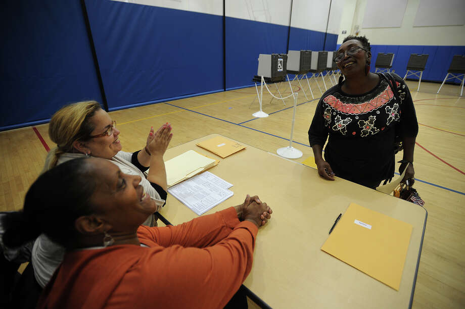 Poll workers Enya Simpson, left, and Providencia Astacio chat with voter Deborah Camp at Cesar Batalla School in Bridgeport, Conn. on Tuesday, September 10, 2013. Photo: Brian A. Pounds / Connecticut Post