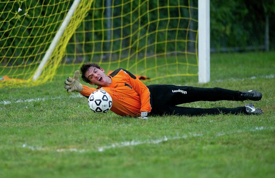 Trinity Catholic goalkeep Tom Gaudioso dives for the ball during a boys soccer game at Trinity Catholic High School on Tuesday, September 10, 2013. Photo: Lindsay Perry / Stamford Advocate