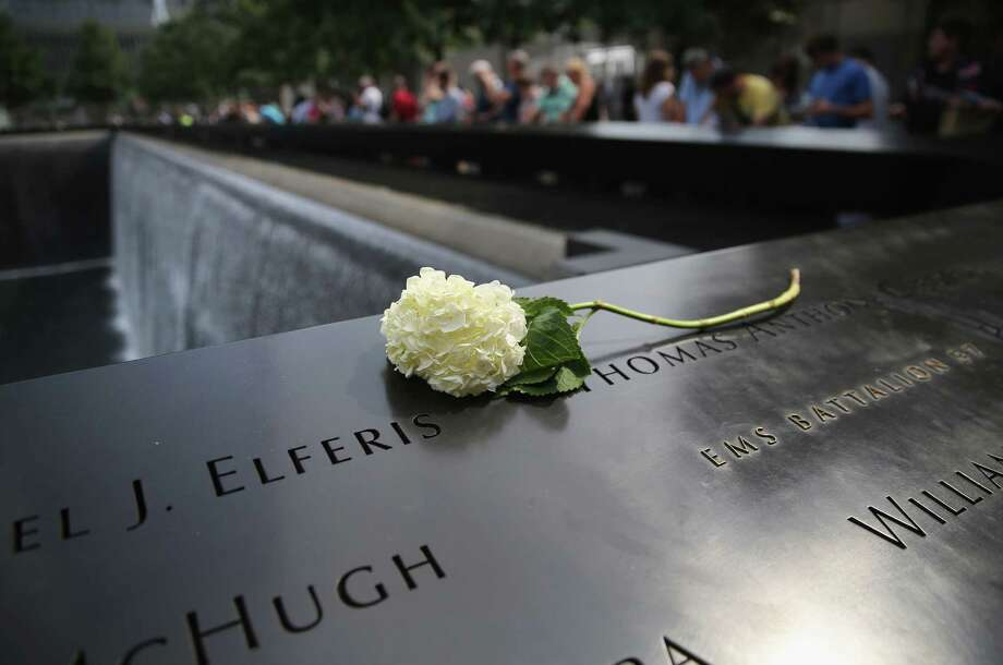 A flower lies atop names of victims at the 9/11 Memorial in New York City. Today marks the 12th anniversary of the attacks of September 11, 2001 that killed nearly  3,000 people. Photo: John Moore, Staff / 2013 Getty Images
