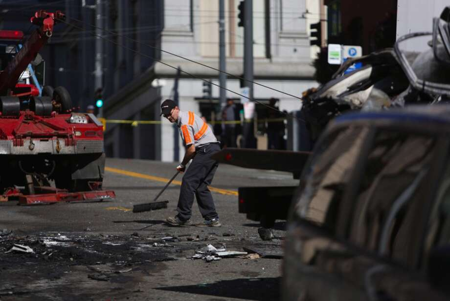 A tow truck crew cleans up the remaining parts of a car that was crushed and burned after a wreck involving a box truck. Photo: JOSHUA TRUJILLO, SEATTLEPI.COM