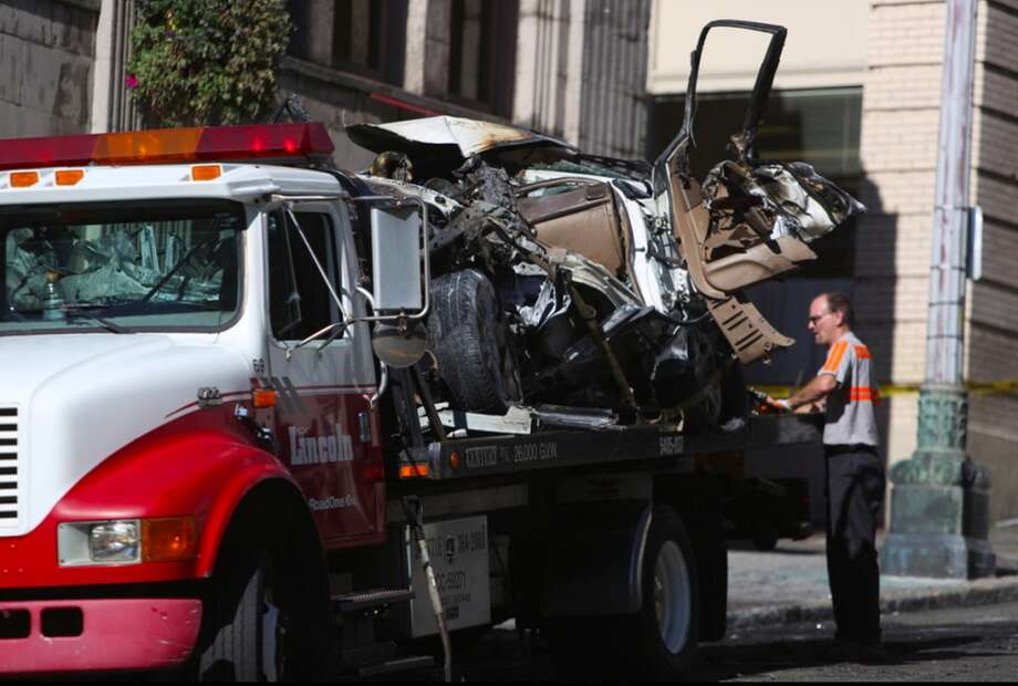 A tow truck crew gathers up the remaining parts of a car that was crushed and burned after a wreck involving a box truck. Photo: JOSHUA TRUJILLO, SEATTLEPI.COM