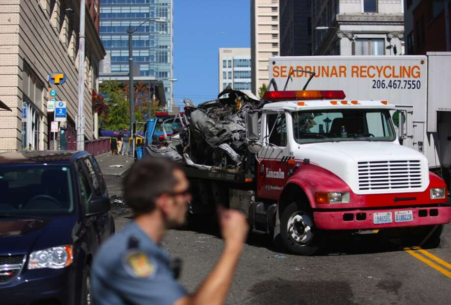 A tow truck crew cleans up after a box truck heading down the hill on James Street crashed into cars near Second Avenue on Tuesday, September 10, 2013. Photo: JOSHUA TRUJILLO, SEATTLEPI.COM