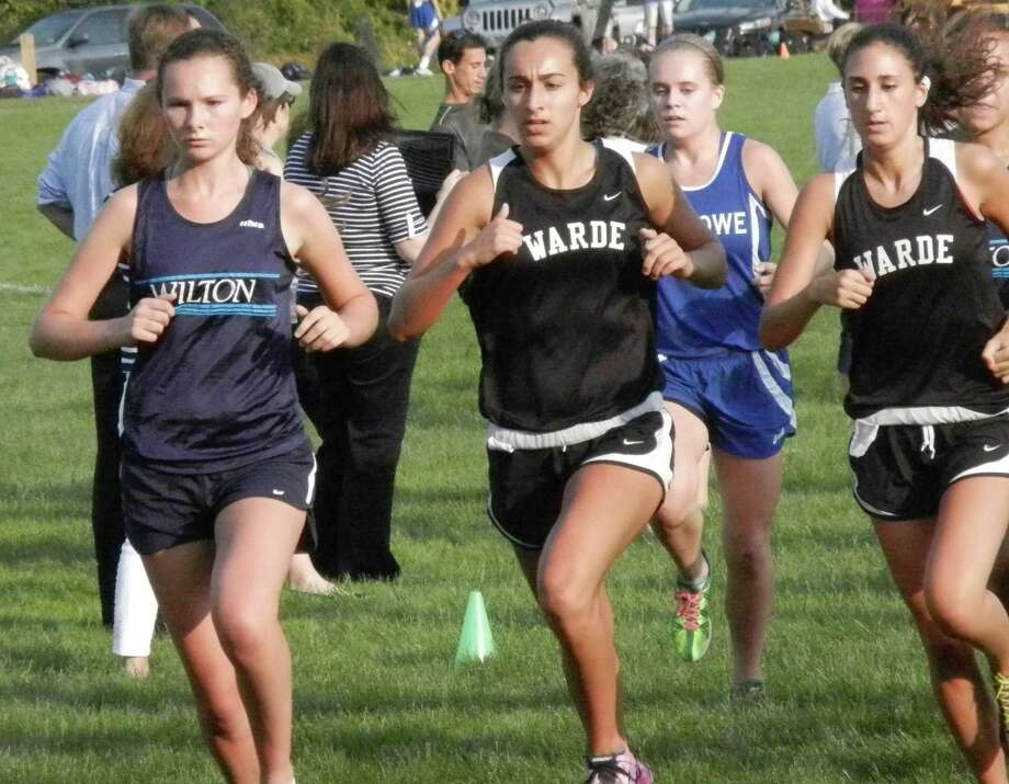 Runners  jockey for position during a cross country quad meet in Wilton Tuesday. From left in the girls' varsity race are an unidentified Wilton runner, Fairfield Warde's Sarah Powlishen, Fairfield Ludlowe's Kelly Walsh and Warde's Roey Mappa. Photo: Reid L. Walmark / Fairfield Citi / Fairfield Citizen