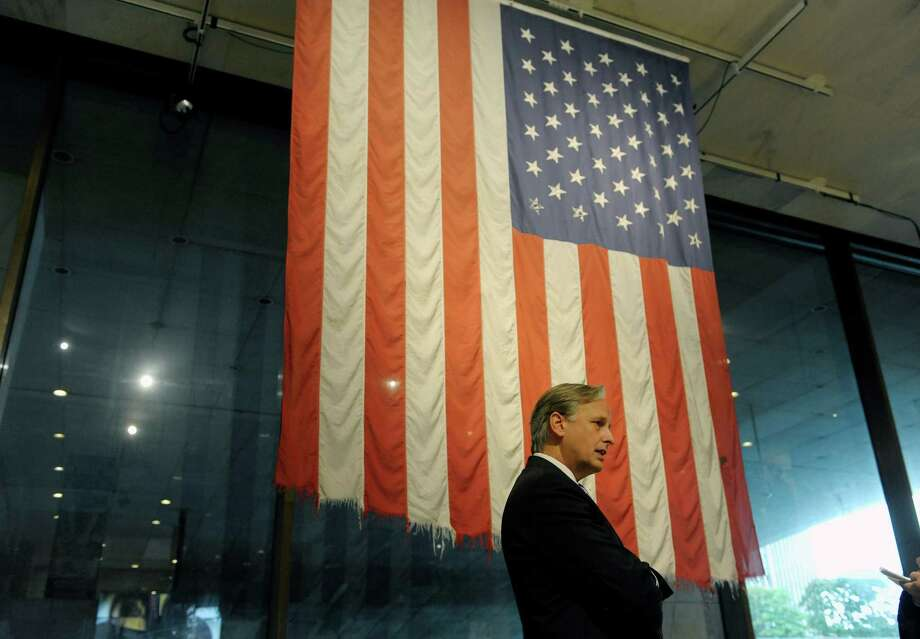 Mark Schaming, director of the New York State Museum stands in front of the Engine 6 flag at the New York State Museum on Tuesday, Sept. 10, 2013 in Albany, NY.  This flag was draped over Engine 6 as it was towed away from the World Trade Center site following the 9/11 attack.  Engine 6 was crushed when the pedestrian bridge it was parked under has collapsed.    (Paul Buckowski / Times Union) Photo: Paul Buckowski / 00023797A