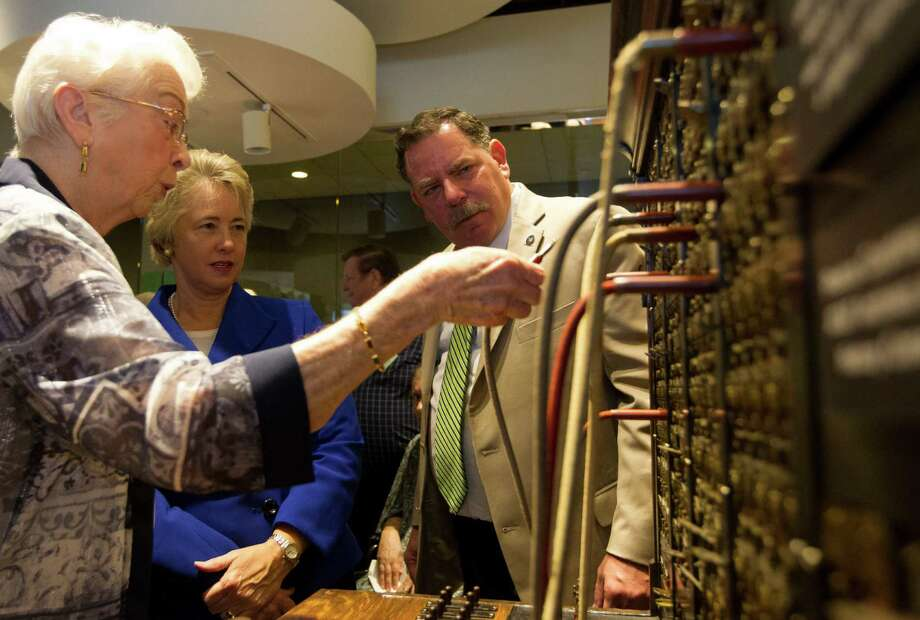 Oleta Porter, left, shows Houston Mayor Annise Parker and Bellaire Mayor Dr. Phil Nauert an old fashion telephone switchboard exhibit at the AT&T local telephone museum at the AT&T headquarters on Tuesday, Sept. 10, 2013, in Bellaire. Photo: J. Patric Schneider, For The Chronicle / © 2013 Houston Chronicle