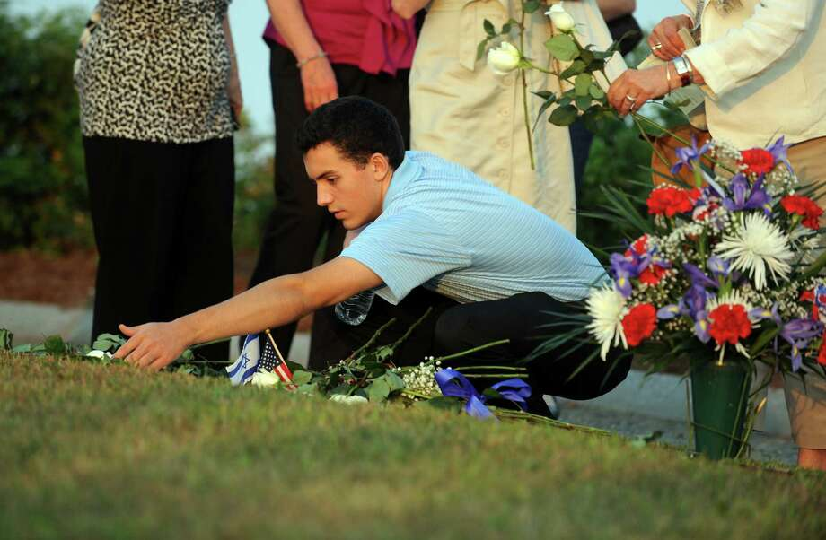 Ryan Faulkner, 19, of Granby, places a flower on his uncle Joseph Anthony Lenihan's memorial stone at Connecticut's 9/11 Living Memorial during the annual 9/11 Memorial Service Tuesday, September 10, 2013 at Sherwood Island State Park in Westport, Conn. Photo: Autumn Driscoll / Connecticut Post
