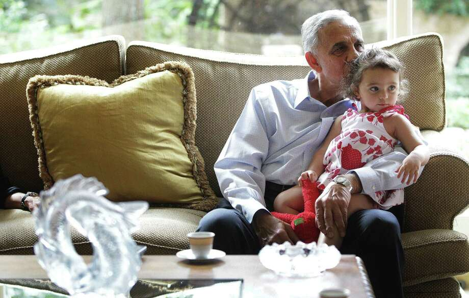 Houston developer Bassam Barazi watches the latest from the country of his birth with granddaughter Leah Abdeen. Photo: Karen Warren, Staff / © 2013 Houston Chronicle