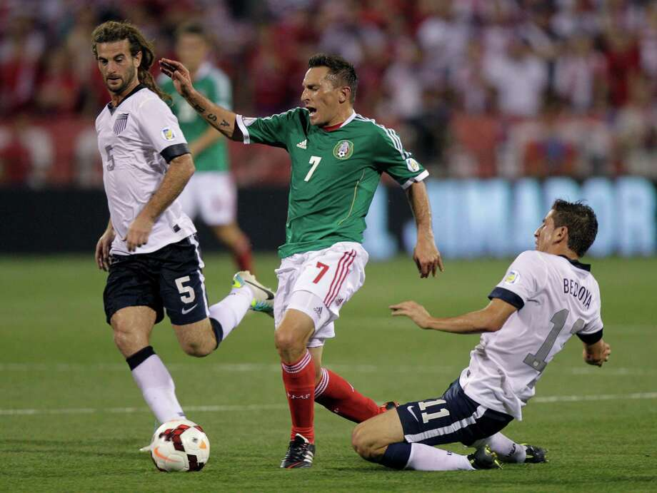 Mexico's Christian Gimenez, center, is tripped by the United States' Alejandro Bedoya, right, as Kyle Beckerman helps to defend during the first half of a World Cup qualifying soccer match Tuesday, Sept. 10, 2013, in Columbus, Ohio. (AP Photo/Jay LaPrete) Photo: Jay LaPrete, Associated Press / FR52593 AP