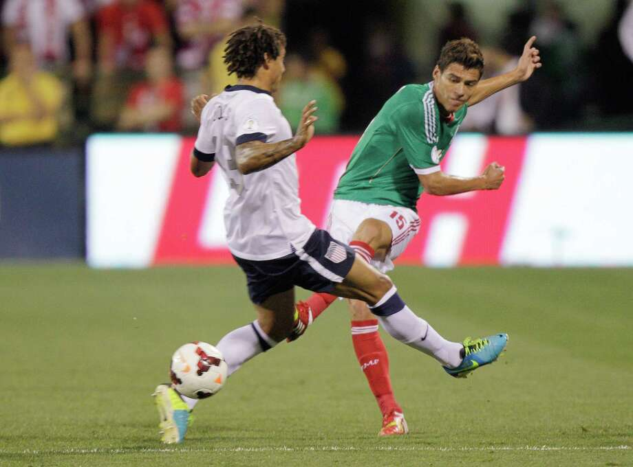Mexico's Hector Moreno, right, shoots the ball past the United States' Jermaine Jones during the first half of a World Cup qualifying soccer match Tuesday, Sept. 10, 2013, in Columbus, Ohio. (AP Photo/Jay LaPrete) Photo: Jay LaPrete, Associated Press / FR52593 AP