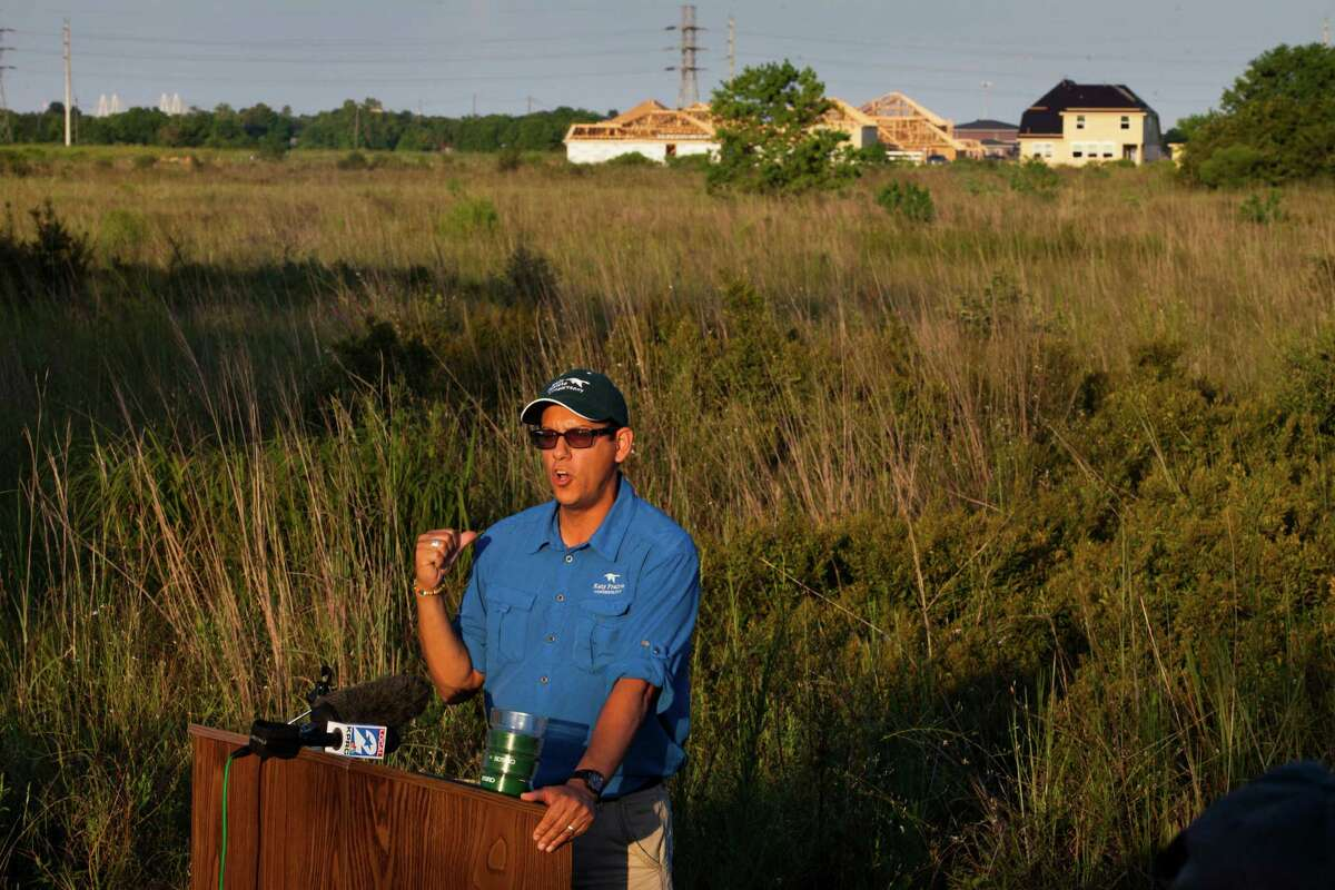 Jaime Gonzé¡lez, conservation education director for the Katy Prairie Conservancy, speaks in the Deer Park prairie - a pristine 50-acre example of one of the world's most endangered ecosystems - which has been saved from development. The Bayou Land Conservancy held a press conference at 6 p.m. to announce the news, Sept. 10, 2013 in Deer Park, TX. In the background are homes being built by developer Dean Lawther. Lawther sold the prairie land to the conservancy and thus saved the pristine prairie.