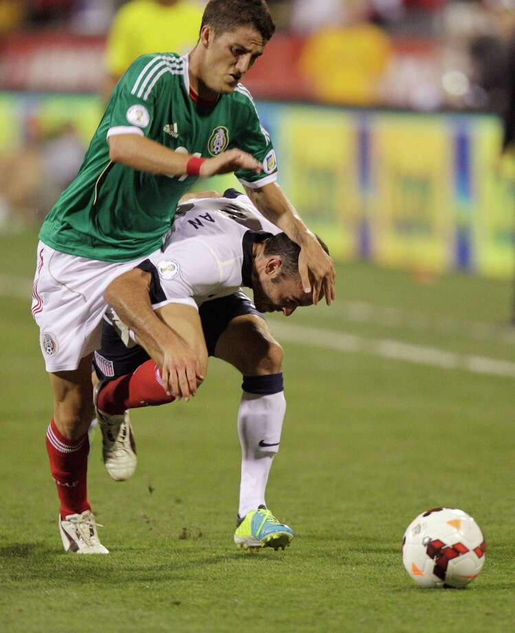 United States' Landon Donovan, right, and Mexico's Hiram Mier race for a loose ball during the second half of a World Cup qualifying soccer match Tuesday, Sept. 10, 2013, in Columbus, Ohio. The United States won 2-0. (AP Photo/Jay LaPrete) Photo: Jay LaPrete, Associated Press / FR52593 AP
