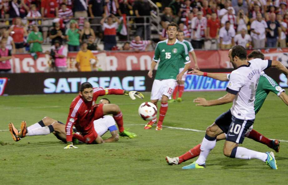 United States' Landon Donovan, right, scores a goal as Mexico goalkeeper Jose de Jesus Corona watches during the second half of a World Cup qualifying soccer match Tuesday, Sept. 10, 2013, in Columbus, Ohio. (AP Photo/Jay LaPrete) Photo: Jay LaPrete, Associated Press / FR52593 AP