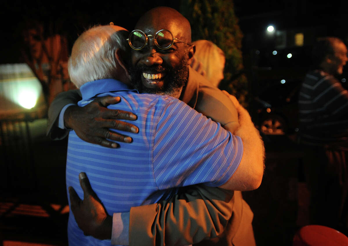 Howard Gardner, facing, is hugged by former city councilman Bob Walsh at the Red Rooster Deli in Bridgeport, Conn. after Gardner and fellow challengers Andre Baker and Dave Hennessey won the Democratic primary for Board of Education on Tuesday, September 10, 2013.