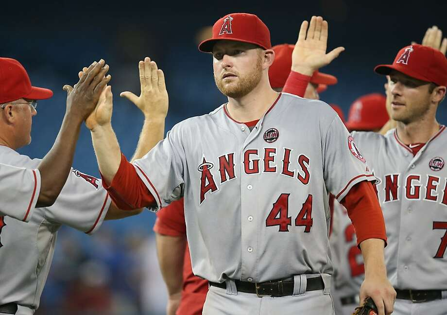 TORONTO, CANADA - SEPTEMBER 10: Mark Trumbo #44 of the Los Angeles Angels of Anaheim celebrates a victory with teammates during MLB game action against the Toronto Blue Jays on September 10, 2013 at Rogers Centre in Toronto, Ontario, Canada. (Photo by Tom Szczerbowski/Getty Images) Photo: Tom Szczerbowski, Getty Images