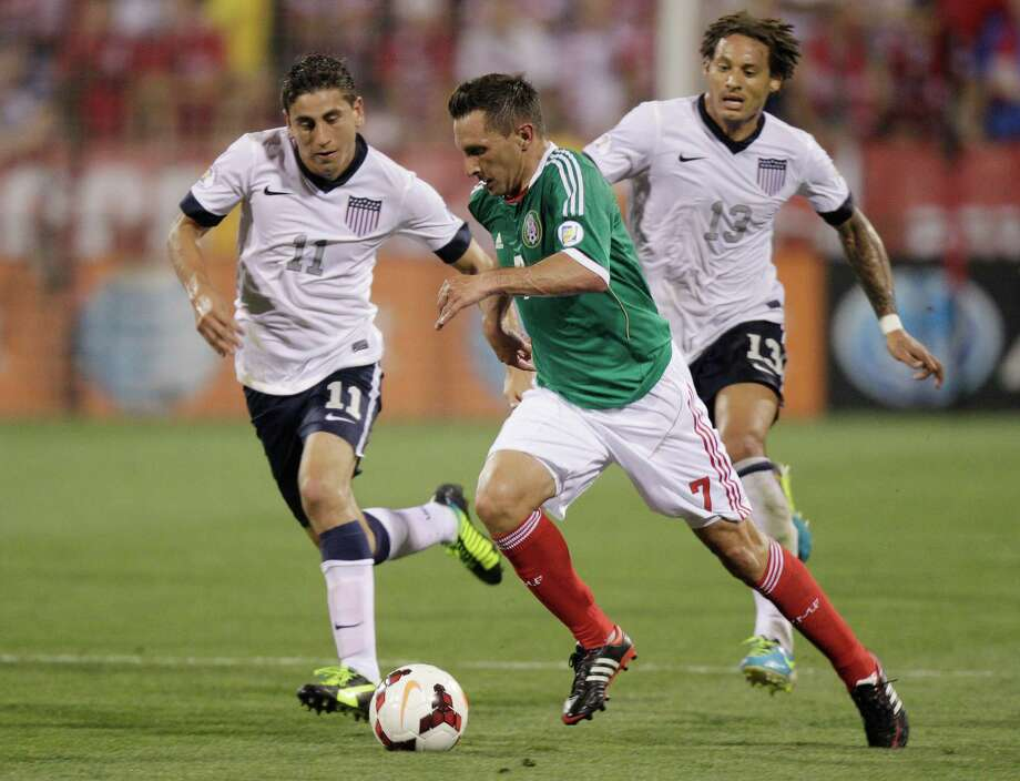 Mexico's Christian Gimenez, center, kicks the ball past United States' Alejandro Bedoya, left, and Graham Zusi during the first half of a World Cup qualifying soccer match Tuesday, Sept. 10, 2013, in Columbus, Ohio. (AP Photo/Jay LaPrete) Photo: Jay LaPrete, Associated Press / FR52593 AP