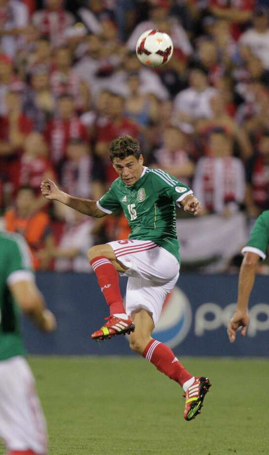 Mexico's Hector Moreno heads the ball against the United States during the first half of a World Cup qualifying soccer match Tuesday, Sept. 10, 2013, in Columbus, Ohio. (AP Photo/Jay LaPrete) Photo: Jay LaPrete, Associated Press / FR52593 AP