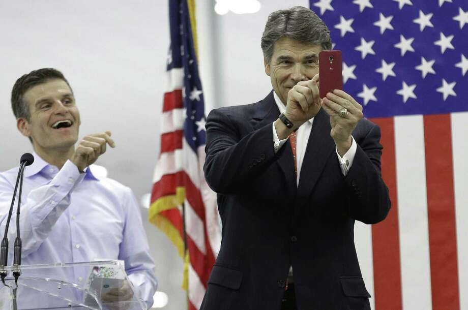 Motorola CEO Dennis Woodside (left) laughs Tuesday as Gov. Rick Perry uses a smartphone given to him during the opening ceremony for a Motorola factory in Fort Worth. Photo: L.M. Otero / Associated Press