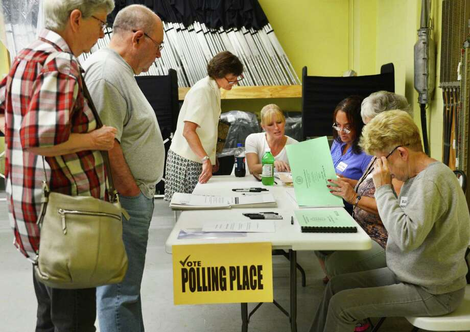 Voters sign in to cast their ballots with election inspectors, at right, Tuesday Sept. 10, 2013, at the Rensselaer County Office Building in Troy, N.Y.   (John Carl D'Annibale / Times Union) Photo: John Carl D'Annibale / 00023798A