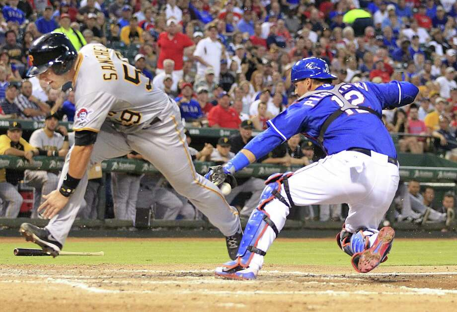 The Pirates' Tony Sanchez stumbles past Rangers catcher A.J. Pierzynski to score in the third inning of Pittsburgh's 5-4 victory. Photo: John Rhodes, STR / Fort Worth Star-Telegram