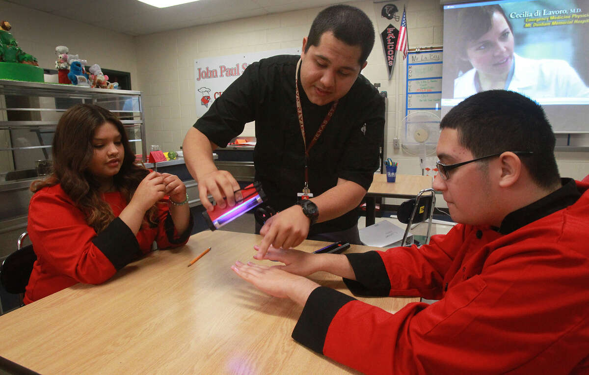 Family Consumer Services teacher David LaBoy teaches class at John Paul Stevens High School Thursday September 5, 2013. LaBoy,23, is a graduate of Stevens High School and is now a teacher there. Seated on the left is student Gabriela Moreno,15, and on the right is student Albert Sotomayor,16.